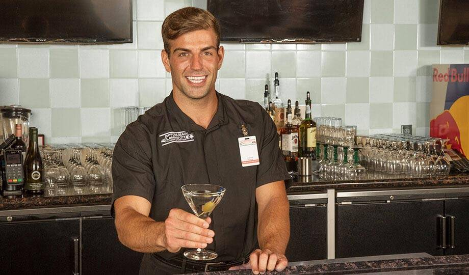 Smiling bartender offering a drink at the Lobby Bar