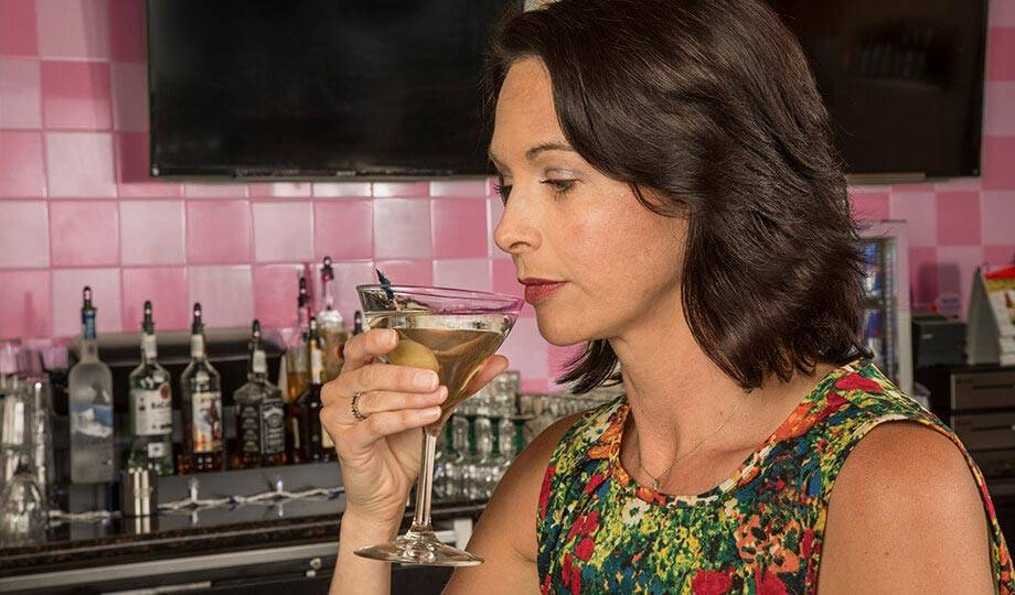 Woman drinking a martini at the Simulcast Bar